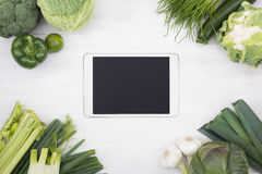 Tablet pc surrounded by vegetables Royalty Free Stock Images