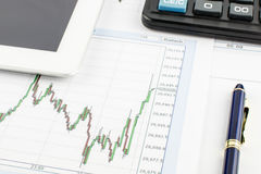 Tablet-PC, Taschenrechner, Stift und Finanzdiagramm auf weißem Hintergrund Stockbilder