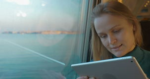 Tablet PC using during traveling by rail. Dolly shot of a woman passenger using tablet computer while traveling by rail. Train going across the bridge, beautiful stock video footage