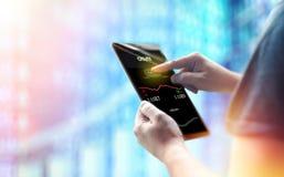 Tablet-PC van de mensenholding tegen financiëngrafieken stock fotografie