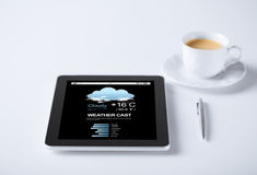 Tablet pc with weather forecast and cup of coffee. Business, meteorology and technology concept - tablet pc computer weather forecast and cup of coffee Royalty Free Stock Photo