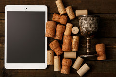 Tablet pc and wine corks Stock Photo