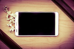 Tablet pc on wood with attributes of cinema. Stock Photo