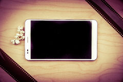 Tablet pc on wood with attributes of cinema. Royalty Free Stock Photos