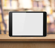 Tablet PC on wood shelf in book shop or library. Tablet PC or ipad on wood shelf in book shop or library stock photo