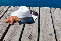 Tablet PC on the wooden swimming dock. Tablet PC, straw hat and sunglasses on the wooden swimming dock Royalty Free Stock Images