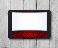 Tablet pc on wooden table with cinema screen displayed. Stock Image