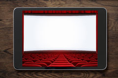 Tablet pc on wooden table with cinema screen displayed. Stock Images