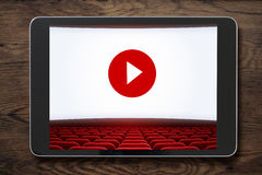 Tablet pc on wooden table with cinema screen displayed. Tablet pc on wooden table with cinema screen with play button displayed. Movies or cinema online concept Royalty Free Stock Photos