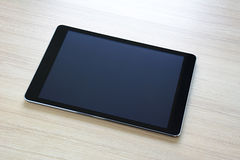 Tablet pc on wooden table Stock Image