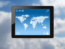 Tablet pc with world map made of clouds Stock Photo