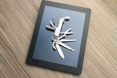 Tablet with penknife. Silver penknife on a tablet screen. Conceptual image for digital tools, multi-task devices, software utilities, innovation and versatility Royalty Free Stock Photos