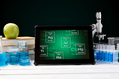Tablet with periodic table symbols Royalty Free Stock Photo