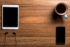 Tablet and phone with coffee on wood with headphones Royalty Free Stock Image