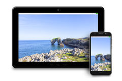 Tablet and phone with photographs of maritime landscapes on whit Royalty Free Stock Image