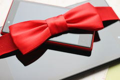 Tablet, phone with red bow, gift. Black tablet computer, red phone and red bow Stock Images