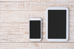 Tablet and phone on white wood Royalty Free Stock Images
