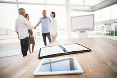 Tablet and planner in front of handshaking business people Stock Photography