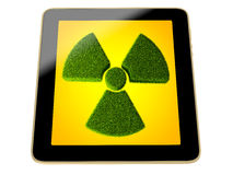 Tablet with radioactivity symbol made from grass on screen Royalty Free Stock Photo