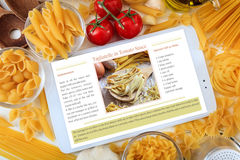 Tablet with recipe on a table with pasta and vegetables. Tablet with pasta recipe on a table with pasta and vegetables Royalty Free Stock Images