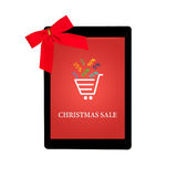 Tablet with red gift bow and christmas sale on a screen Stock Photography
