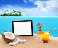 Tablet and refreshments in the beach. Tablet, coconut and cocktail in the sand Royalty Free Stock Photos