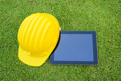 Tablet and Safety helmet. On the greenfield. copy space for advertising Stock Image