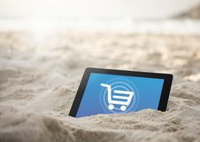 Tablet in the sand beach with Shopping trolley icon Stock Image