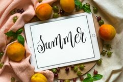 The tablet says the word SUMMER with fresh fruits on the wooden background. Concept of the summer, View from above. Copy Space. stock photo