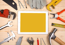Tablet and set of plumbing and tools on the wooden table Stock Photo