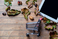 Tablet, shopping cart and fallen leaves Stock Image