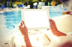 With tablet sitting at swimming pool Royalty Free Stock Photography