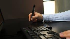 Tablet 23 Sluit omhoog van de hand van een grafische ontwerper gebruikend elektronische naald en toetsenbord voor het werk Linker stock footage