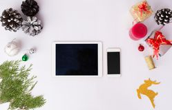 Tablet smart phone display on table on white screen for mockup in Christmas time. Christmas tree, decorations in background. Tablet smart phone display on table Royalty Free Stock Photos