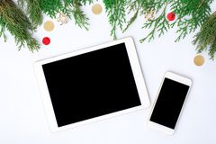 Tablet smart phone display on table on white screen for mockup in Christmas time. Christmas tree, decorations. Colorful and elegant theme for branding Royalty Free Stock Image