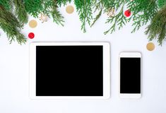 Tablet smart phone display on table on white screen for mockup in Christmas time. Christmas tree, decorations. Colorful and elegant theme for branding Stock Photography