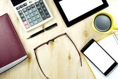 Tablet and smart phone on office work desk, Top view working wood table Royalty Free Stock Images