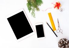 Tablet smart phone on white screen for mockup in Christmas time. Christmas tree, decorations in background. Tablet smart phone display on table on white screen Stock Photography