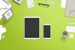 Tablet and smartphone with blank screen for mockup surrounded with stationery and office supplies Stock Photo