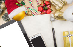 Tablet, smartphone and open notebook with winter ornaments. Royalty Free Stock Photography
