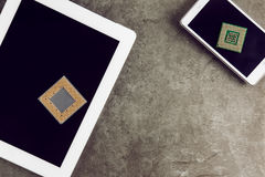 Tablet And Smartphone With Processors. Tablet And Smartphone With Two Processors On Granite Surface With Empty Screen stock photos