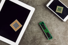 Tablet And Smartphone With Processors. Tablet And Smartphone With Two Processors And Memory Chip On Granite Surface With Empty Screen royalty free stock image