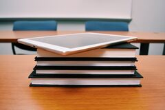 Tablet on stack of books in classroom Stock Image
