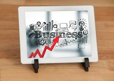 Tablet on stand showing red arrow with black business doodles against blurry background Royalty Free Stock Image