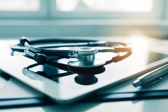 Tablet and stethoscope on white table. Medicine and technology concept. Tablet and stethoscope on white table. Medicine and modern technology concept royalty free stock photography
