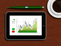 Tablet with the stock chart lying on a wooden table Royalty Free Stock Photo