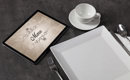 Elegant laid table with stylish restaurant logo. Tablet with stylish restaurant logo and laid tablen royalty free stock images