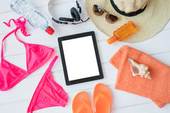 Tablet and sunbathing kit Stock Photos