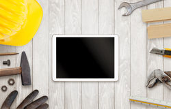 Tablet surrounded by construction tools stock photography
