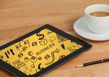 Tablet on table with coffee showing black business doodles and yellow background Stock Photo